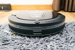 Robot vacuum cleaner on laminate wood and carpet.