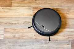 Robot vacuum cleaner on the parquet floor Stock Photography