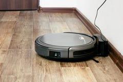 Robot vacuum cleaner on the parquet floor Stock Photos