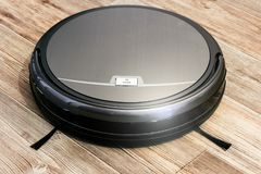Robot vacuum cleaner on the parquet floor Royalty Free Stock Photos
