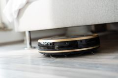 Robot vacuum cleaner runs under bed Stock Photos