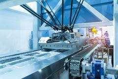 Robot with vacuum suckers with conveyor in manufacture factory stock photo