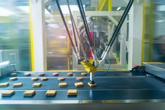 Robot with vacuum suckers with conveyor in Production of cookies. In a manufacture factory for the food industry stock images