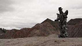 Robot walking in a desert landscape. Footage. Android robot in the mountain desert in cloudy weather.  stock video