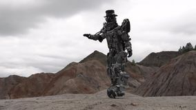 Robot walking in a desert landscape. Footage. Android robot in the mountain desert in cloudy weather.  stock footage