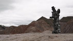 Robot walking in a desert landscape. Footage. Android robot in the mountain desert in cloudy weather.  stock video footage