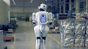 Robot is walking through the factory facility from backside view. Robot is walking through the factory premises for backside view. 4K stock video footage