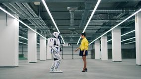 A robot walks towards a woman and takes her hand. stock footage