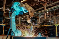 Robot is welding metal part in car factory royalty free stock image