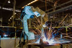 Robot is welding metal part in car factory royalty free stock photos