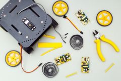 Robot on wheels and  yellow tools. Flat lay stock photography