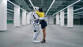 Robot and woman hugging each other, standing in an empty room. stock video