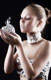 Robot woman with metallic apple. On dark background Royalty Free Stock Image