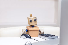 Robot working at a computer and used e mouse at the table Stock Images