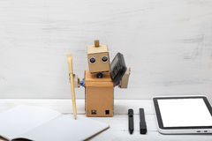 The robot works, talking on the phone and writes in a notebook Royalty Free Stock Image