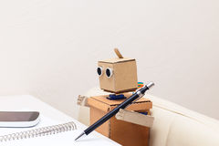 Robot writes with a ballpoint pen at the table. Robot writes with a ballpoint pen  at the table at home Royalty Free Stock Images