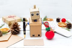 Robot writes pen congratulations on a postcard with christmas an. D holds a Christmas tree toy. horizontal Royalty Free Stock Photos