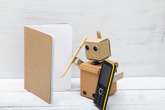 Robot writes a pen in a notebook and talking on the phone Royalty Free Stock Photography