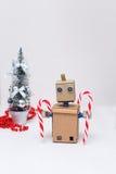 Robot y piruletas y árbol del Año Nuevo en el fondo blanco Imágenes de archivo libres de regalías