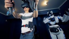 Robot y videojugador que se levantan en vidrios de VR, cierre