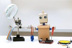 Robot z jego wręcza trzymać śrubokręt obok kłamstwa i inny Zdjęcia Royalty Free