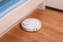 Robota próżniowy cleaner biega pod łóżkiem w sypialni Fotografia Stock