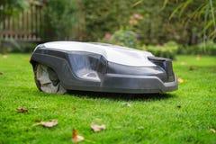 Robotachtig grasmaaimachine scherp gras in de tuin stock afbeeldingen