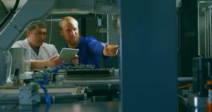 Robotachtige ingenieurs die machines in pakhuis 4k controleren stock video