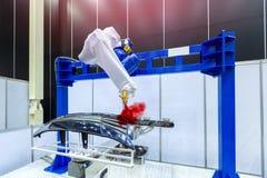 Robotachtige wapen het schilderen nevel aan het automobieldeel Hoog-Technolo royalty-vrije stock fotografie