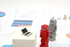 Robotar eller konstgjord intelligens och bärbar dator på grafer och diagram Royaltyfri Fotografi