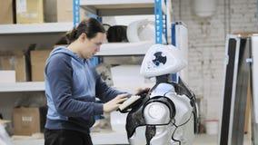 Robotar för fabrik för tillverkning av Forskaren reflekterar på apparaten av roboten Ställer in - upp och gör justeringar arkivfilmer