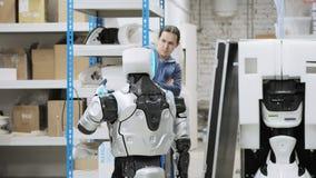 Robotar för fabrik för tillverkning av Forskaren reflekterar på apparaten av roboten Ställer in - upp och gör justeringar lager videofilmer