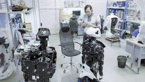 Robotar för fabrik för tillverkning av, moderna robotic utvecklingar En grupp av unga teknikerer skapar nya moderna robotar arkivfilmer