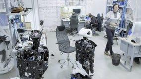 Robotar för fabrik för tillverkning av, moderna robotic utvecklingar En grupp av unga teknikerer skapar nya moderna robotar stock video