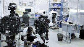 Robotar för fabrik för tillverkning av, moderna robotic utvecklingar En grupp av unga teknikerer skapar nya moderna robotar lager videofilmer