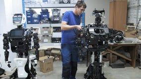 Robotar för fabrik för tillverkning av Teknikern fäster en separat del av handen till kroppen av den nya roboten stock video
