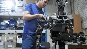 Robotar för fabrik för tillverkning av Teknikern fäster en separat del av handen till kroppen av den nya roboten lager videofilmer