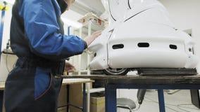 Robotar för fabrik för tillverkning av Teknikern fäster en separat del till kroppen av den nya roboten Skapar en robot stock video