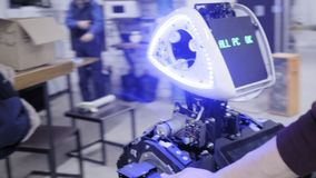 Robotar för fabrik för tillverkning av Teknikern flyttar roboten till och med växten Kör roboten till ett annat seminarium stock video