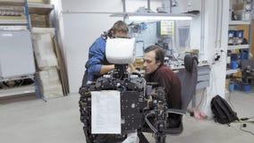 Robotar för fabrik för tillverkning av Två teknikerer undersöker en robot Skapar en ny robot i labbet reparationer stock video