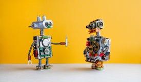 Robotar på gul bakgrund 4th automationbegrepp för industriell revolution Robotic militär med skruvmejseln som är idérik arkivfoton