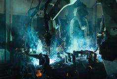 Robotar som svetsar i en bilfabrik Royaltyfri Bild