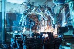Robotar som svetsar i en bilfabrik Arkivbilder