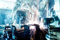 Robotar som svetsar i en bilfabrik Arkivfoto