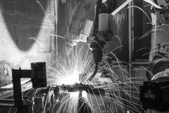 Robotar som svetsar i en bilfabrik, black&white Royaltyfri Fotografi