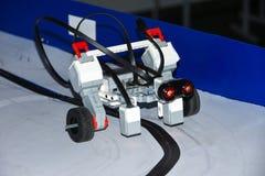 Robotbilen som är församlad från formgivare, specificerar ritter på den magnetiska vägen av startup studenter arkivbild