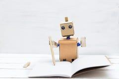 Roboten i handen rymmer pennan och skriver i dagboken Lig Arkivbild