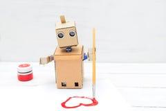 Roboten rymmer en borste i hans hand och drar den på en vit shee Fotografering för Bildbyråer