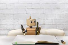 Roboten skriver i dagbokpenna i svart sammanträde på tabellen Royaltyfri Bild