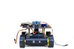 Roboter auf Rädern mit verschiedenen Drähten auf einem hellen Hintergrund Stockbilder
